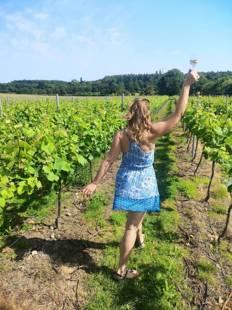 janina doyle in the squerryes vineyards holding glass of sparkling english wine