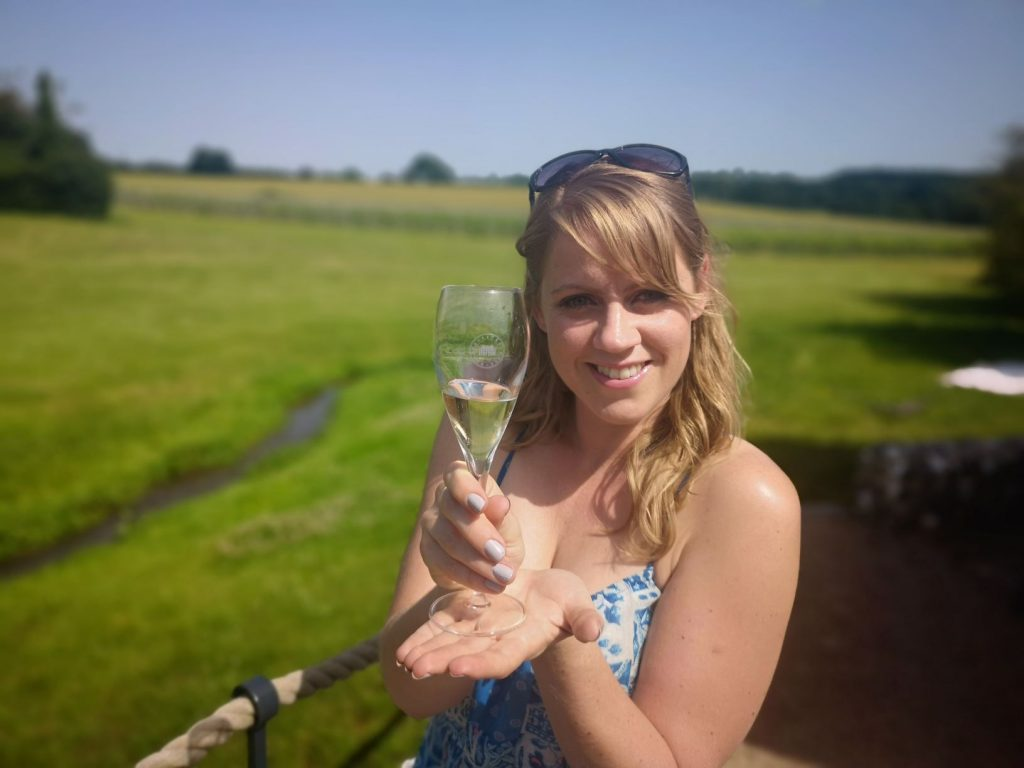 janina doyle with glass of sparkling english wine from Squerryes Winery